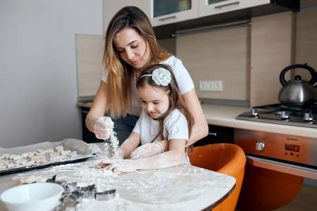 Mother and her adorable kid have fun in the kitchen, close up photo.lifestyle, free time, spare time