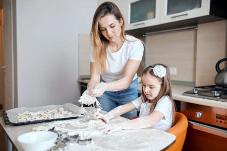 young woman and her daughter learning to make dough, pastry. close up photo. entertainment, upbringing