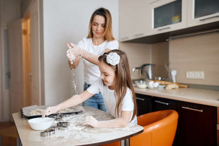 little girl and her mother having flour party, girl likes to help her mother in the kitchen. close up side view photo. family cooking dessert according to grannys recipe 版權商用圖片