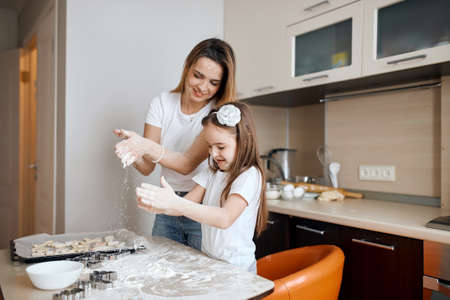 positive little girl and woman making cookies in the kitchen. family making a cake, close up side view photo