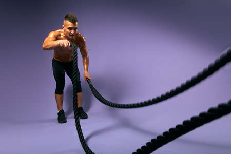 tired sportsman concentrated on doing exercises with ropes, guy preparing for a competition. full length photo. copy space.isolated blue background, fitness, crossfit