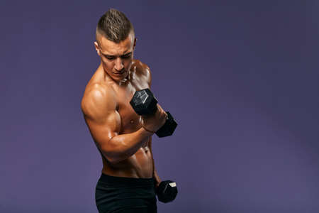 muscular ambitious motivated athletic man with weight, isolated on blue, close up portrait, copy space. health and body care,free time, spare time, hobby, interest