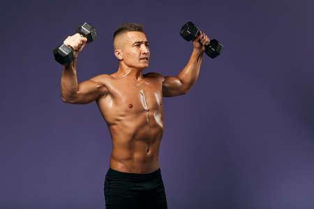 serious man with tensed musculars raising his arms while workout with sport equipment. close up side view photo, isolated blue background . copy space, breaking record, effort 版權商用圖片