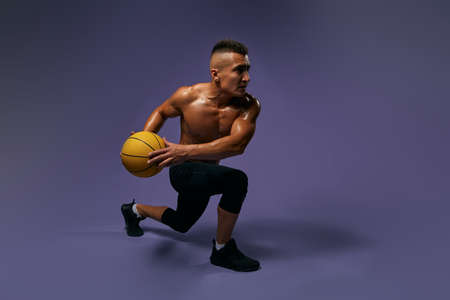 sweaty handsome man learning to play basketball, full length photo, isolated blue background, studio shot, lifestyle, free time, spare time
