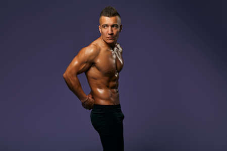 sexy tanned guy with stylish hairdo is being proud of his well-built body, result of active life, close up portrait, man is being on a diet, health care, copy space, isolated blue background