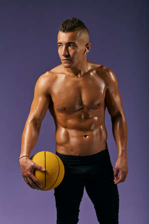 Portrait of confident young handsome sportsman with basket ball standing against blue background. looking aside close up portrait,lifestyle, free time, spare time,