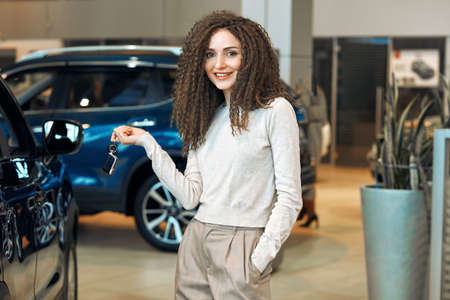 wide varity of second hands vehicles are available at the salon, . dreams come true, close up photo. confident shop assistant offer luxury car. blue car in the background of the photo