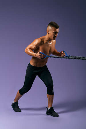 strong shirtless man training with expander, guy is keen of fitness, man preparing for a competition, full length side view photo. isolated blue background, studio shot