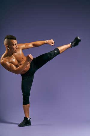 Man biting ips, training taekwondo, kickboxing at sport center Isolated on blue background, full length photo, isolated blue, studio shot, motivation, strength training, health and body care 版權商用圖片