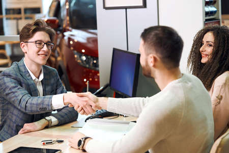 auto business, car sale, technology, gesture and people concept - cheerful family shaking hands with dealer at auto show, agreement. close up photo. bargain, thank you 版權商用圖片