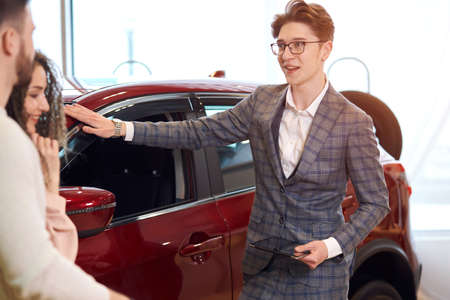 young smart man recommending family to buy red car, bargain, advise close up photo.