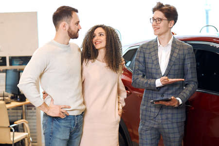 auto business, car sale, technology and people concept young man showing car options for man and woman, welcome.