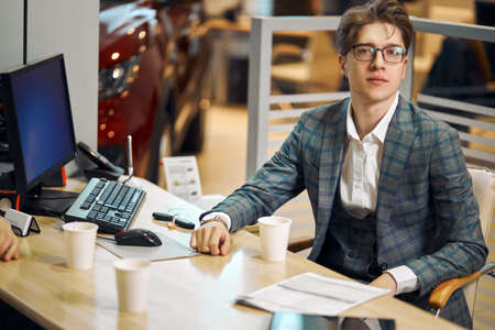 young successful handsome man in glasses sitting at workplace, close up photo. work, job, occupation, working hours. day, he is looking at the camera