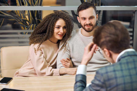 elegant stylish business man having a meeting with a couple sitting together at a table in the office, family going to take loan, renting a flat, booking a room, hotel. close up photo. conversation