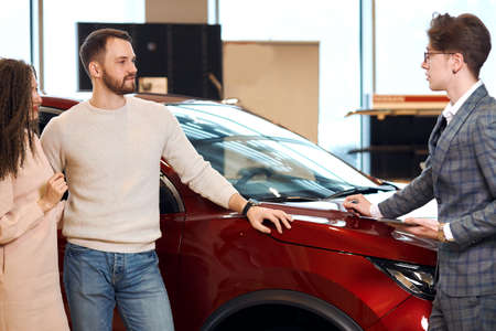young couple thinking about buying a car, close up photo. dealer and clients standing in front of the red car at dealership. close up photo Foto de archivo