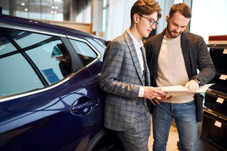 happy man buying a new car at vehicle showroom, close up photo. conversation with a professional talented dealer, dealer cheating with documents, paper. Stockfoto