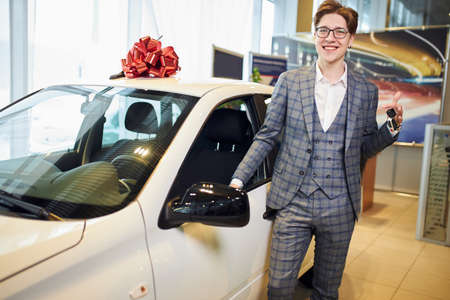 Happy handsome stylish dealer in gray checvked suit holding car keys. close up photo. luxury white car waiting for you. close up photo. happiness, business, car sale.red bow is on the top of white car