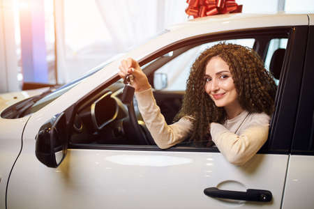 smiling attractive girl has got a new car on St.Valentines day, close up photo. bargain, girl is boasting with her new vehicle. Dreams come true. Positive emotions, Auto Business , Car Selling