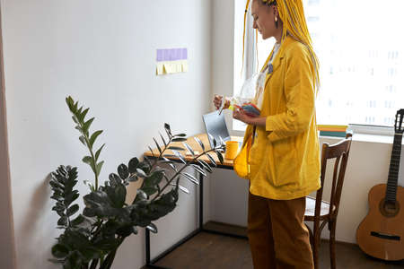 Young stylish woman in yellow deads holding color stickers in office. close up side view photo. free lancer planning her day. job, profession, time management