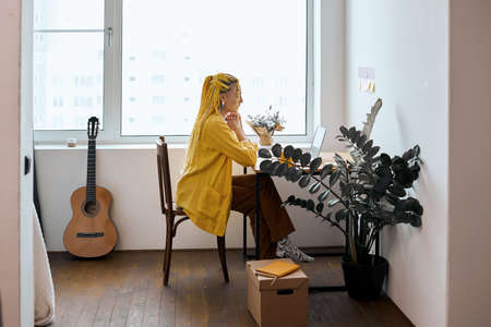 young attractive talented girl is keen on writing stories, poems, having a consultation online, education, full length side view photo. guitar in the background of the photo. business