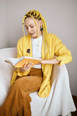 attractive girl with stylish yellow dreads enjoying reading book, close up photo, vertical shot. hobby, interest, lifestyle, free time, spare time, lifestyle, girl having rest, favourite book, writer