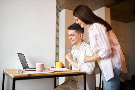 young couple using laptop at home, watching webinar,workshop, close up side view photo. family styding, training seminar. side view photo