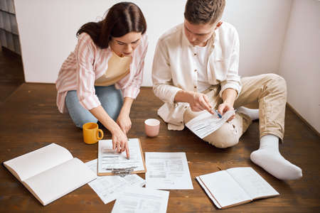 young family analizing their badget, close up photo. free time, spare time, lifestyle.paper work, brunette woman pointing to the document Foto de archivo