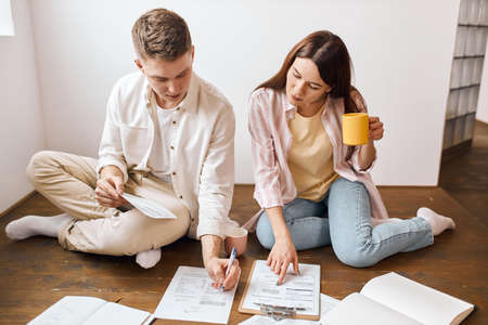 young man and woman making statistic financial report, sit at floor in modern apartment, look through documents,