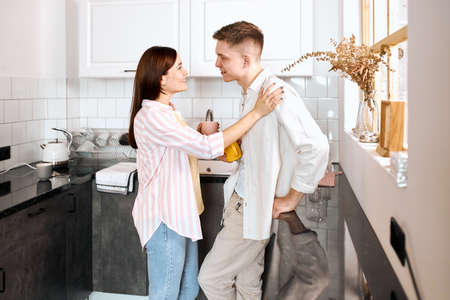 cheerful attractive family having conversation in the kitchen, close up side view photo. free time, spare time, lifestyle, smiling woman support her boyfriend, touching his arm, cheering him up Foto de archivo