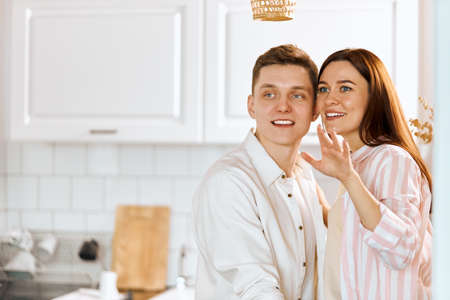 young cheerful happy couple standimg in the kicthen, close up photo. copy space, family dreaming about successful reach luxury life. excited young people looking aside, common ideas, goals