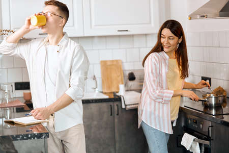 handsome guy drinking coffee, his girlfriend preparing healthy breakfast, household duties. close up side view photo. lifestyle, interest