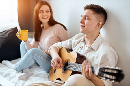 young handsome man enjoying playing the guitar, happy girl with long brown hair drinking coffee and listening to him, close up side view photo