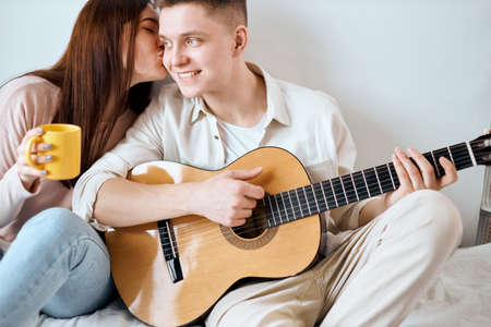 young pleasant girl kissing her husband who is entertaining her with musical instrument, girl thanking her man for musicla present, serenade, close up photo