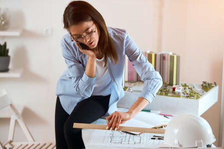 Successful attractive engineer drawing house draft and making a phone call Woman multi-tasking.close up photo, girl sitting on the edge of the table and measuring scetch, Banco de Imagens