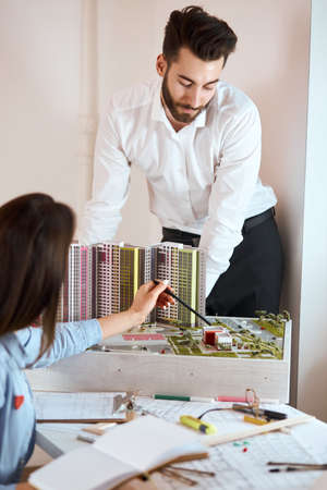young man and woman having a discussion about new building complex, cooperative. vertical shot. close up photo