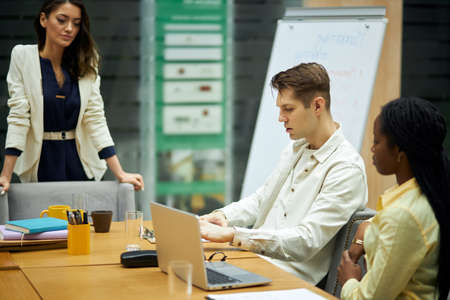 young blonde serious guy discussing problems with his coworkers in the office room with modern interior. close up side view photo.unpleasant situation, failure concept