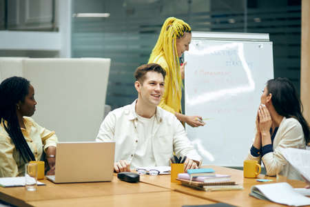 glamour woman with yellow dreads explaining her point of view on the problem while her colleagues are laughing at her, happiness, positive mood, atmosphere at the meeting