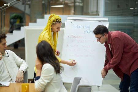 young couple teaching the secrets of marketing to new employees, close up photo. management, woman writing information about marketing