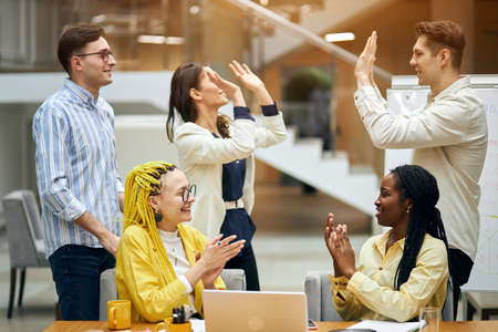 cheerful active ambitious people congratulating each other, booming business, negotating successful contract with foreign company. good job, well done