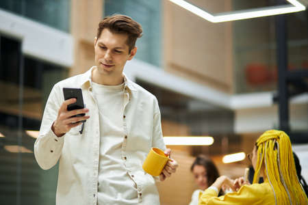 Smiling handsome young man using smart phone, texting message, typing sms, surfing the net, internet. close up photo. blurred background. copy space