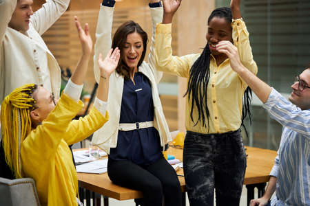 business people raising hands celebrating success in office, rejoicing at victory, booming business, compant has earned much money, happiness, well doen, good job, emotion, feeling, reaction