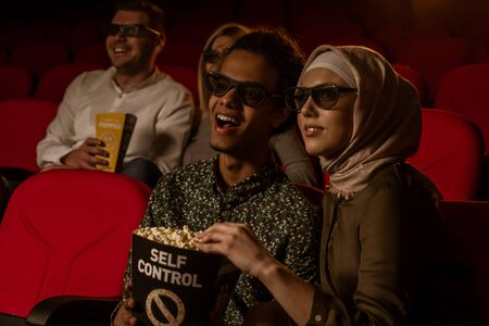 African american muslim man with his wife sitting in movie theater, watching 3D movie, eating popcorn, smiling.