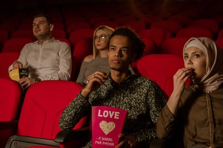 African american muslim man with his wife sitting in movie theater, watching movie, eating popcorn, smiling.