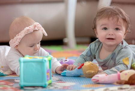 cute twins, baby girl and baby boy playing with toys by the home
