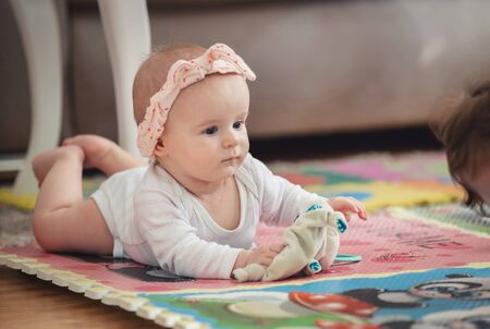 A cute young baby playing inside home with colorful toys