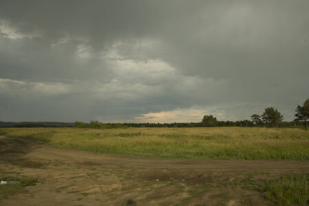 Empty road with thunderclouds on background field, rain Stock Photo