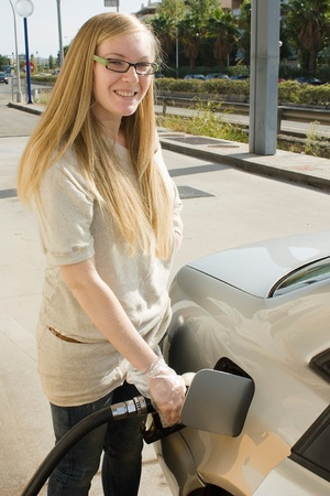 refuel: Woman holding fuel nozzle and refuel car in gas station  Stock Photo