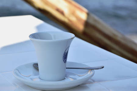 White cup of coffee and the sea in a background
