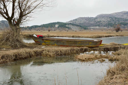 Old fishing boat on the shore of the lake