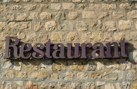 Written Restaurant on the stone wall. Stock Photo